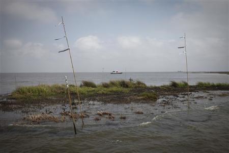 A work boat passes an oiled marshland, one year after the BP Oil Spill, in Bay Jimmy near Myrtle Grove, Louisiana, April 20, 2011. REUTERS/Lee Celano