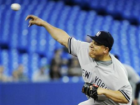 New York Yankees pitcher Bartolo Colon throws against the Toronto Blue Jays during the third inning of their American League MLB baseball game in Toronto April 20, 2011. REUTERS/Mark Blinch