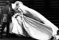 <p>Lady Diana Spencer, soon to become the Princess of Wales, showing her wedding gown for the first time, turns as her bridesmaids set her train on arrival at Saint Paul's Cathedral for her wedding to Prince Charles in London, July 29, 1981. REUTERS/Mal Langsdon</p>