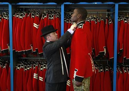 Irish Guardsman Bortnill St'Ange is fitted with his ceremonial uniform by Master Tailor Lance Sergeant Matthew Else at their barracks in Windsor, southern England April 21, 2011. REUTERS/Eddie Keogh