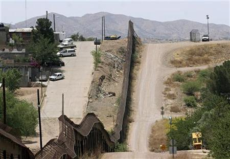 A U.S. Border Patrol agent (upper right) waits in his jeep at his post near the wall that separates Nogales, Sonora, Mexico (left of wall) from Nogales, Arizona on the U.S. and Mexican border in this May 21, 2006 file photo. REUTERS/Jeff Topping