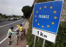 <p>Велосипедисты разговаривают около дорожного знака на итальянско-француской границе 25 апреля 2011 года. Франция и Италия хотят реформировать Шенгенское соглашение и усилить агентство Евросоюза Frontex, которое обеспечивает внешнюю безопасность границ, сказал во вторник президент Франции Николя Саркози. REUTERS/Eric Gaillard</p>