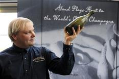 <p>Christian Ekstrom, the diver that found the world's oldest champagne is pictured with a bottle of it in this photograph made available to Reuters, April 25, 2011. Two bottles of champagne, part of a cache of about 150 that were salvaged from a 19th century shipwreck in the Baltic Sea, will be auctioned in Finland in June. REUTERS/Daniel Eriksson/Handout</p>