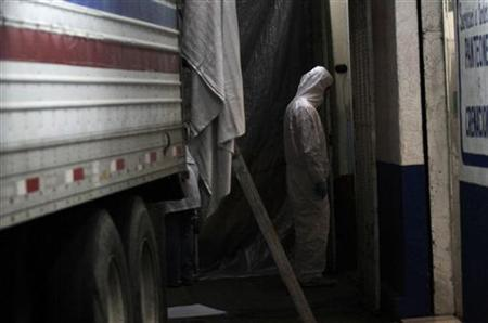 A forensic worker stands next to a truck parked outside the La Piedad embalming building in Mexico City, and containing 50 bodies found in a mass grave in northern Mexico, April 19, 2011. REUTERS/Carlos Jasso