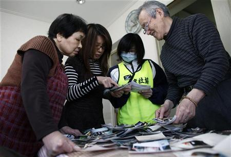 Tsunami victim Yasuo Miura (R), his wife Noriko (L) and daughter Yuka (2nd L) look at their photographs, which were washed away by the March 11 earthquake and tsunami, after receiving them from volunteer Atsuko Sato in Ofunato, Iwate prefecture, April 18, 2011. REUTERS/Toru Hanai