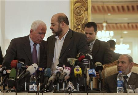 Azzam al-Ahmad, head of the Fatah group (L), changes seats with Mousa Abu Marzook (C), a senior member of Hamas, near Mahmoud al-Zahar (R), a co-founder of Hamas and a member of the Hamas leadership in the Gaza Strip, during a news conference in Cairo, April 27, 2011. REUTERS/Asmaa Waguih