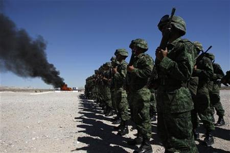 Soldiers stand in formation as marijuana and other drugs are being incinerated at a military base in Ciudad Juarez March 2, 2011. REUTERS/Gael Gonzalez