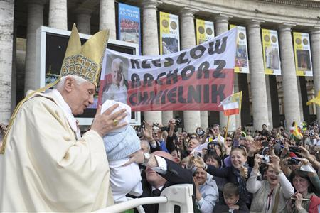 Pope Benedict XVI kisses a baby as he arrives to celebrate a mass for the beatification of Pope John Paul II in Saint Peter's Square at the Vatican May 1, 2011. REUTERS/Osservatore Romano