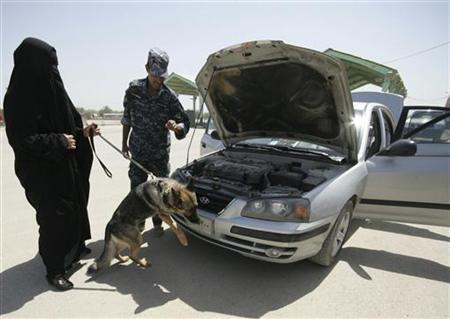 A policewoman uses a bomb-sniffer dog to check a vehicle as policeman looks on during a training course at a police academy in Kerbala, 80 km (50 miles) southwest of Baghdad April 27, 2011. REUTERS/Mushtaq Muhammed