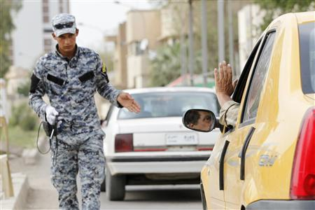 An Iraqi policeman uses a scanning device to inspect vehicles passing through a checkpoint in Baghdad May 2, 2011. REUTERS/Mohammed Ameen