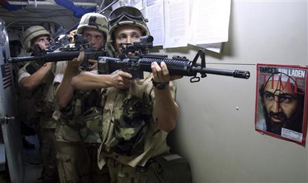 U.S. Special Operation Capable (SOC) Marines with the 26th Marines Expeditionary Unit (MEU), patrol past a picture of Osama bin Laden as they practice urban combat and room clearing in their quarters aboard the USS Whidbey Island, off the coast of Pakistan, December 12, 2001. REUTERS/Patrick Baz/Pool