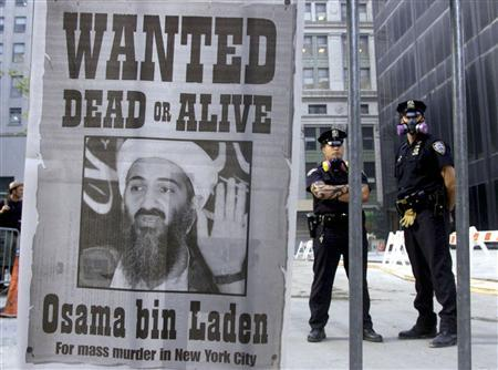 Police stand near a wanted poster of Saudi-born militant Osama bin Laden, printed by a New York newspaper, in New York in this September 18, 2001 file photograph. REUTERS/Russell Boyce/Files