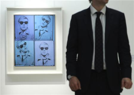 A Christie's employee poses for a photograph with artist Andy Warhol's ''Self-Portrait'' at Christie's auction house in London April 15, 2011. REUTERS/Luke MacGregor
