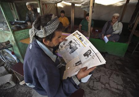 An Afghan man reads a newspaper article on Osama Bin Laden's death, at a roadside tea shop in Kabul, May 3, 2011. REUTERS/Ahmad Masood