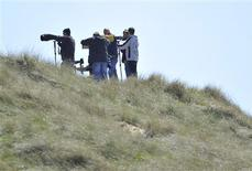<p>Photographers stand on dunes near the perimeter of RAF Valley near Holyhead in Anglesey, north Wales, May 3, 2011. REUTERS/Toby Melville</p>