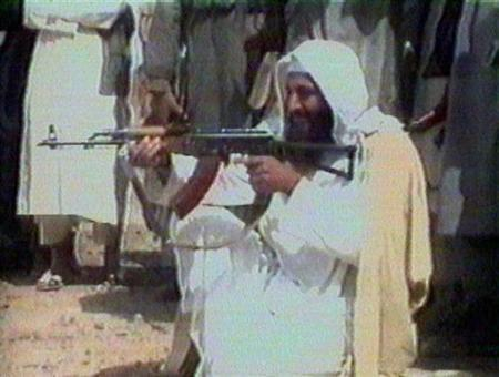 Osama bin Laden aims a weapon at an undisclosed location on an undated video obtained by Kuwaiti newspaper al-Rai al-Aam in 2001. REUTERS/File