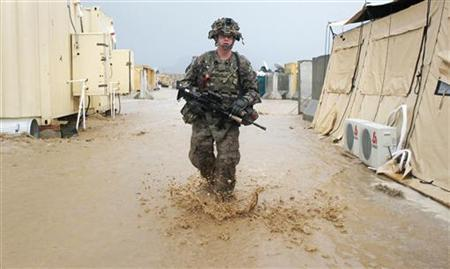 A U.S. Army soldier walks through water after a flash flood swept through Combat Outpost Terra Nova following heavy rains in the Arghandab Valley north of Kandahar April 16, 2011. REUTERS/Bob Strong