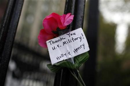 A flower and message hangs on a fence on Church street near the World Trade Center site in New York, May 3, 2011. REUTERS/Mike Segar