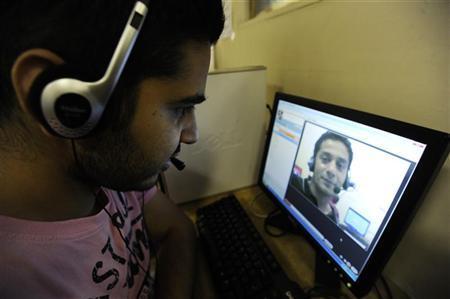 Zubair Ghumro (L) speaks to his friend Sheeraz Qazalbash using Skype software at an internet cafe in central London August 10, 2010. REUTERS/Paul Hackett