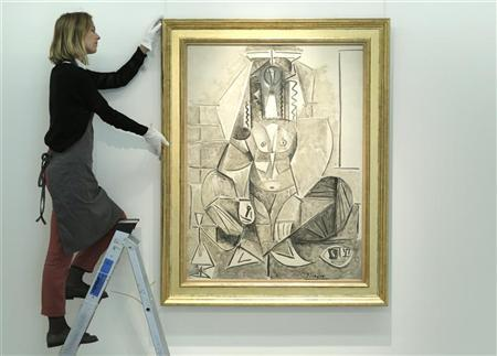 A Christie's employee poses with artist Pablo Picasso's ''Les Femmes d'Alger'' at Christie's auction house in London April 15, 2011. REUTERS/Luke MacGregor