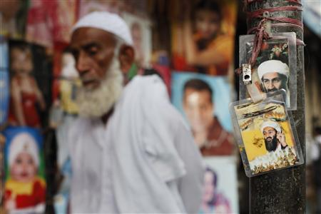 A man walks past images of al Qaeda leader Osama bin Laden displayed near a poster shop selling his images in Karachi May 4, 2011. REUTERS/Athar Hussain