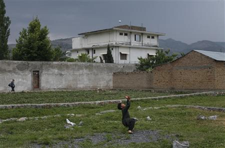 Local resident Adeel, 8, plays with a tennis ball in front of the compound where Osama bin Laden was killed in Abbottabad, May 5, 2011. REUTERS/Akhtar Soomro