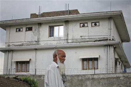A resident walks past the compound where SEAL commandos reportedly killed al Qaeda leader Osama bin Laden in Abbottabad May 5, 2011. REUTERS/Akhtar Soomro