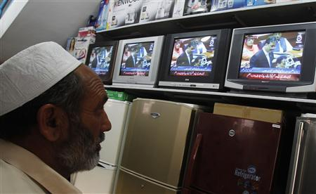A man watches Pakistan's Prime Minister Yusuf Raza Gilani on a televised address to the parliament at an appliance store in Islamabad, May 9, 2011. REUTERS/Erik de Castro