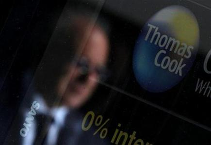 A pedestrian is reflected in the window of a branch of travel agent Thomas Cook in London May 9, 2011. REUTERS/Luke MacGregor