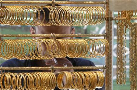 A man looks at gold jewellery displayed at a shop in Amman's gold market April 25, 2011. REUTERS/Ali Jarekji