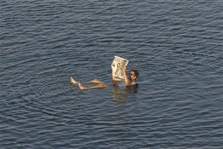 A tourist reads a newspaper as he floats in the Dead Sea resort of Ein Gedi May 20, 2010. REUTERS/Baz Ratner