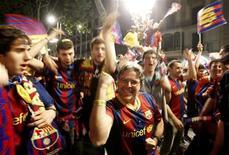 """<p>Болельщики """"Барселоны"""" празднуют победу команды в чемпионате Испании, 11 мая 2011 года. Каталонская """"Барселона"""" сыграла вничью с """"Леванте"""" и досрочно стала чемпионом Испании - третий раз кряду. REUTERS/Gustau Nacarino</p>"""