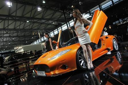 Models pose next to a Spyker C8 Aileron during the Shanghai Auto Show April 20, 2011. REUTERS/Aly Song