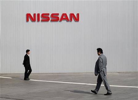 Men walk past a Nissan logo at the company's global headquarters in Yokohama, February 9, 2011. REUTERS/Toru Hanai
