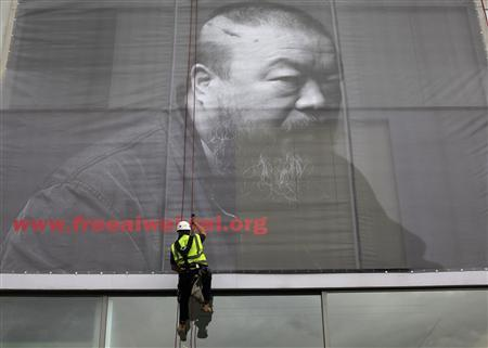 A worker attaches a banner showing Chinese artist Ai Weiwei, to the Lisson Gallery in London May 11, 2011. REUTERS/Andrew Winning