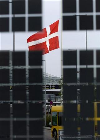 A Danish flag is seen through a glass-wall flying at half mast in front of Copenhagen Airport October 8, 2001.REUTERS/Christian Charisius