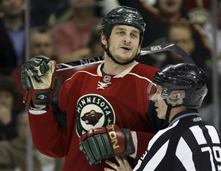 Minnesota Wild left wing Derek Boogaard is held back by linesman Mark Pare during the second period of their NHL hockey game against the Vancouver Canucks in St. Paul, Minnesota in this January 13, 2010 file photo. REUTERS/Eric Miller/Files