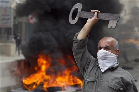 A Palestinian protester holds up a symbolic key during clashes with Israeli security forces at Qalandiya checkpoint, near the West Bank city of Ramallah May 15, 2011. REUTERS/Darren Whiteside