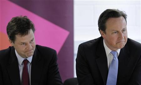 Prime Minister David Cameron (R) and Deputy Prime Minister Nick Clegg speak to company representatives during a round-table meeting with business leaders in a room at the handball arena, at the 2012 London Olympic Park, in London May 12, 2011. REUTERS/Matt Dunham/Pool