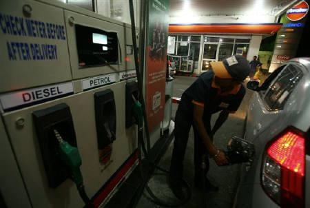 A worker fills petrol in a car at a fuel station in Jammu May 14, 2011. REUTERS/Mukesh Gupta