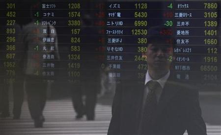 A man is reflected on an electronic board at a brokerage in Tokyo April 27, 2011. REUTERS/Yuriko Nakao