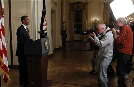 Photographers take pictures of President Barack Obama after he announced live on television the death of Osama bin Laden, from the East Room of the White House in Washington May 1, 2011. REUTERS/Jason Reed