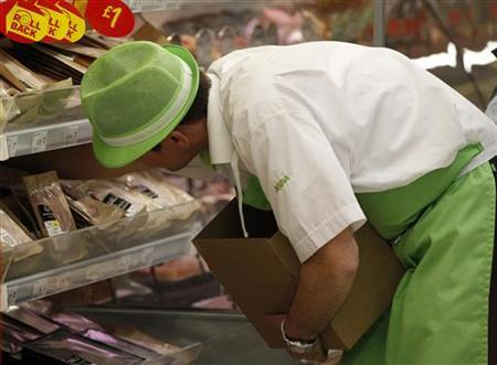 A worker fills shelves at an ASDA supermarket in Oldham, northern England, January 5, 2011. REUTERS/Phil Noble