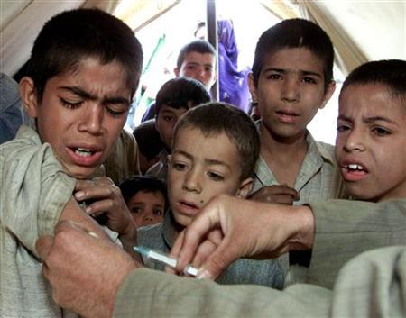 An Afghan medical assistant gives a measles vaccine to a boy in a refugee camp east of Kabul May 5, 2002. REUTERS/Vasily Fedosenko