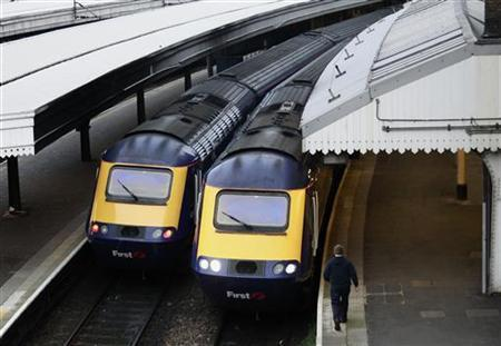 A worker passes First Great Western trains at Paddington Station in London November 21, 2010. REUTERS/Luke MacGregor