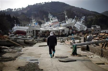 A man walks next to port area destroyed by the earthquake and tsunami in Kessenuma town, in Miyagi prefecture, March 28, 2011. REUTERS/Carlos Barria