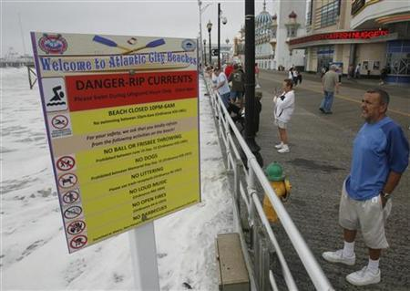 A storm watcher stands near the warning sign for swimmers on the boardwalk in Atlantic City, New Jersey, September 3, 2010. REUTERS/Tim Shaffer