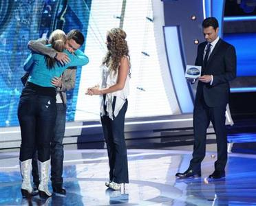 Eliminated contestant Haley Reinhart looks on as Scotty McCreery hugs Lauren Alaina as the two advance to the final of ''American Idol'', May 19, 2011. REUTERS/Michael Becker/FOX