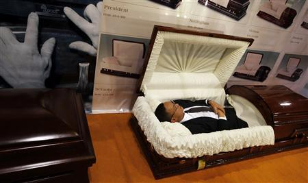 A TV journalist tries a coffin during the Asia Funeral Expo (AFE) in Hong Kong, May 19, 2011. REUTERS/Bobby Yip