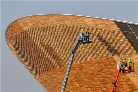 Construction workers add wooden panelling to the outside of the velodrome at the London Olympic site in Stratford in east London November 18, 2010. REUTERS/Toby Melville